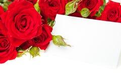 Rosas rojas y tarjeta en blanco de la invitación Imagenes de archivo
