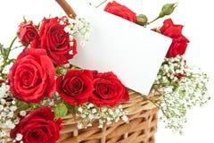 Rosas rojas y tarjeta en blanco en cesta de mimbre Foto de archivo libre de regalías
