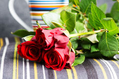Rosas rojas y taza Fotografía de archivo libre de regalías