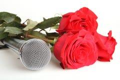 Rosas rojas y un micrófono Imagen de archivo