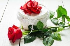 Rosas rojas y una caja con un regalo fotografía de archivo