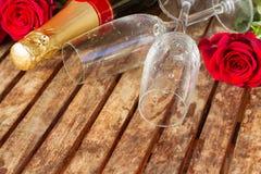 rosas rojo oscuro con el cuello del champán Foto de archivo libre de regalías