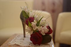 Rosas rojo oscuro en zapato verde en el talón en la tabla en sitio Fotografía de archivo