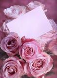 Rosas rosadas con una tarjeta de felicitación Foto de archivo libre de regalías