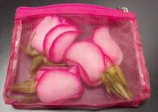 Rosas rosadas en bolso cosmético Imagenes de archivo
