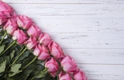 Rosas rosadas en el fondo de madera blanco con el espacio de la copia Visión superior Fotos de archivo libres de regalías