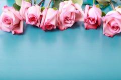 Rosas rosadas en el tablero de madera de los azules turquesa imagenes de archivo