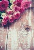 Rosas rosadas en el viejo tablero de madera Fotografía de archivo