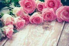 Rosas rosadas en el viejo tablero de madera Imagen de archivo libre de regalías