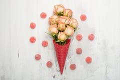 Rosas rosadas en un cono rojo con el helado en un fondo de mármol, regalo para el fondo festivo querido, aniversario del concepto fotos de archivo libres de regalías