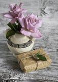 Rosas rosadas en un florero de cerámica con el ornamento griego, caja de regalo hecha en casa Foto de archivo libre de regalías