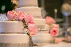 Rosas rosadas en un pastel de bodas Fotografía de archivo libre de regalías