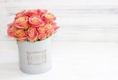 Rosas rosadas hermosas en una caja redonda Rosas del melocotón en una caja redonda Rosas en una caja redonda en un fondo de mader Imagenes de archivo