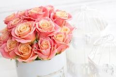 Rosas rosadas hermosas en una caja redonda Rosas del melocotón en una caja redonda Rosas en una caja redonda en un fondo de mader Fotos de archivo libres de regalías