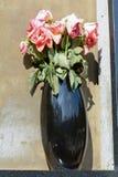 Rosas rosadas marchitadas en florero Imagenes de archivo
