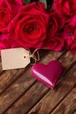 Rosas rosadas oscuras con los corazones y la etiqueta Foto de archivo libre de regalías