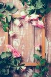 Rosas rosadas y un marco de madera Imágenes de archivo libres de regalías