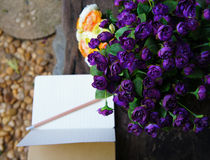 Rosas roxas e amarelas artificiais com um livro de nota aberto Fotografia de Stock Royalty Free
