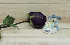 Rosas secas e boneca cerâmica no fundo de madeira do teste padrão Fotografia de Stock Royalty Free