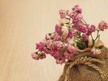 Rosas secas, rosas secadas, rosas rosadas secas borrosas en saco marrón en el piso de madera, rosas del vintage, concepto de amor Fotografía de archivo