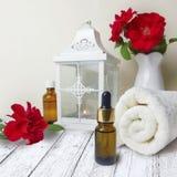Rosas, toalla, linterna, botella de aceite esencial en la tabla de madera foto de archivo