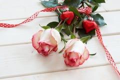 Rosas vermelhas amarradas com uma fita e corações Imagem de Stock