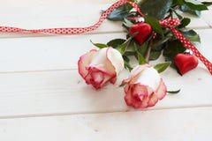 Rosas vermelhas amarradas com uma fita e corações Fotografia de Stock Royalty Free
