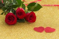 Rosas vermelhas bonitas com corações decorativos em um fundo do ouro imagens de stock royalty free