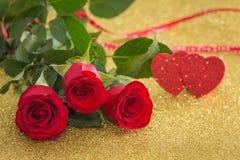 Rosas vermelhas bonitas com corações decorativos em um fundo do ouro fotografia de stock