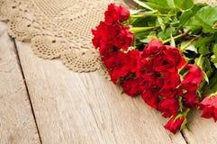 Rosas vermelhas bonitas em uma tabela de madeira Fotografia de Stock