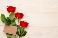 3 rosas vermelhas com o cartão de papel do ofício vazio Foto de Stock Royalty Free