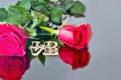 Rosas vermelhas com reflexão no espelho e na inscrição: AMOR Valentine& x27; tema do dia de s Momentos românticos Imagens de Stock