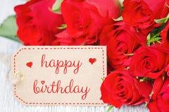 Rosas vermelhas de cartão de aniversário e uma etiqueta com feliz aniversario do texto Fotos de Stock