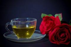 Rosas vermelhas e chá no vidro fotografia de stock