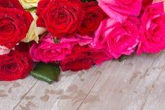 Rosas vermelhas e cor-de-rosa na tabela Imagem de Stock Royalty Free