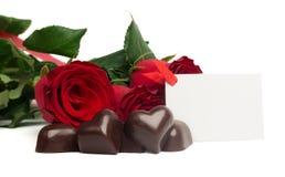 Rosas vermelhas e doces em uma forma de um coração Fotos de Stock