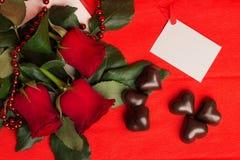 Rosas vermelhas e doces em uma forma de um coração Fotografia de Stock