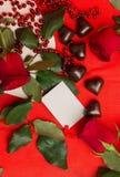 Rosas vermelhas e doces em uma forma de um coração Foto de Stock