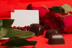 Rosas vermelhas e doces em uma forma de um coração Fotografia de Stock Royalty Free
