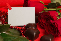 Rosas vermelhas e doces em uma forma de um coração Imagem de Stock Royalty Free
