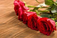 Rosas vermelhas em seguido na tabela Fotos de Stock Royalty Free