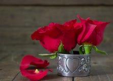 Rosas vermelhas na tabela velha no suporte de prata antigo do serviette do coração Fotografia de Stock