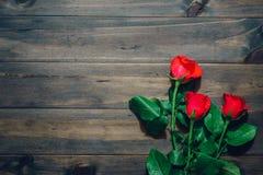 Rosas vermelhas no fundo de madeira escuro Configuração lisa Vista superior com bobina Imagens de Stock