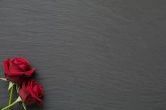 Rosas vermelhas no fundo vazio da ardósia Fotos de Stock