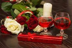 Rosas, vidrios de vino y una caja con una joya teniendo en cuenta velas Fotos de archivo libres de regalías