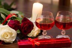 Rosas, vidrios de vino y una caja con una joya teniendo en cuenta velas Imagen de archivo libre de regalías