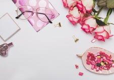 Rosas y accesorios femeninos lindos en la tabla blanca, Foto de archivo libre de regalías