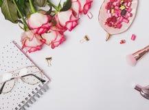 Rosas y accesorios femeninos lindos en la tabla blanca Imágenes de archivo libres de regalías