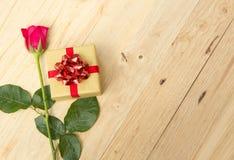 Rosas y cajas de regalo en un piso de madera Foto de archivo libre de regalías