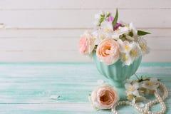 Rosas y flores en colores pastel del jazmín en florero en la turquesa b de madera Imagen de archivo